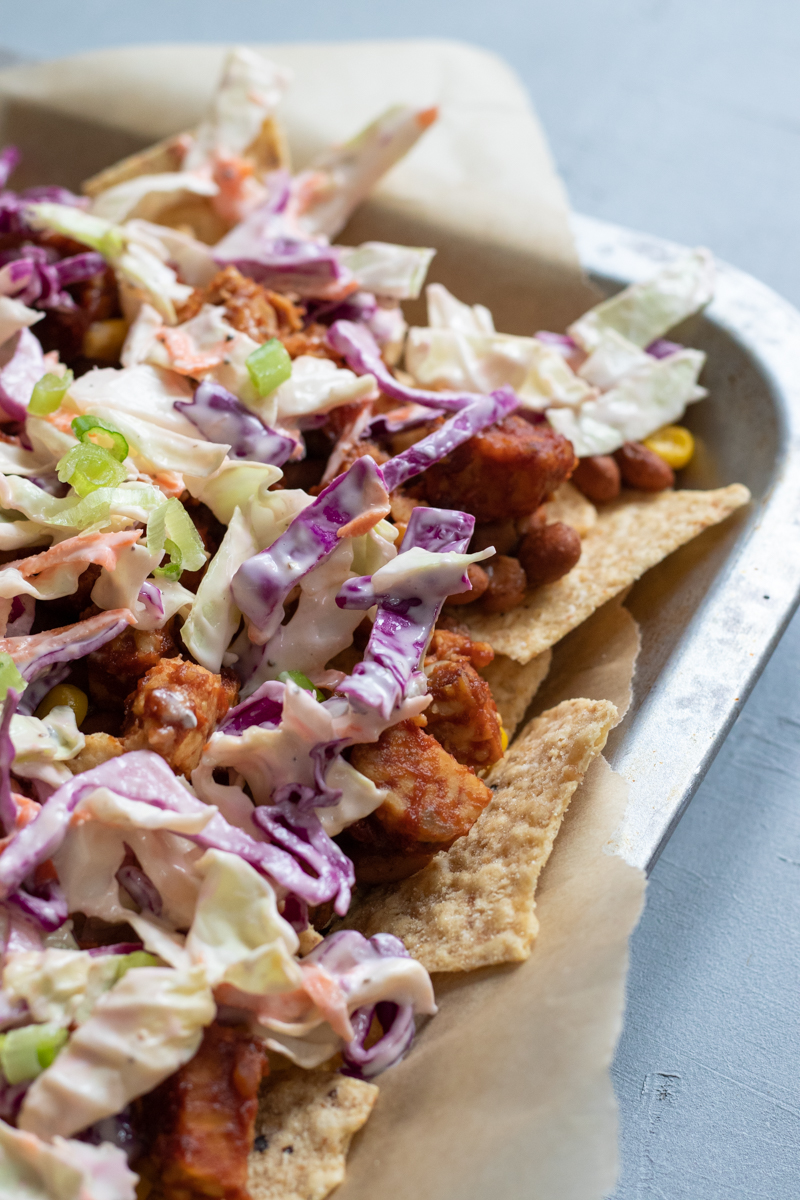 start by layering tortilla chips, then beans, tempeh, and slaw; repeat