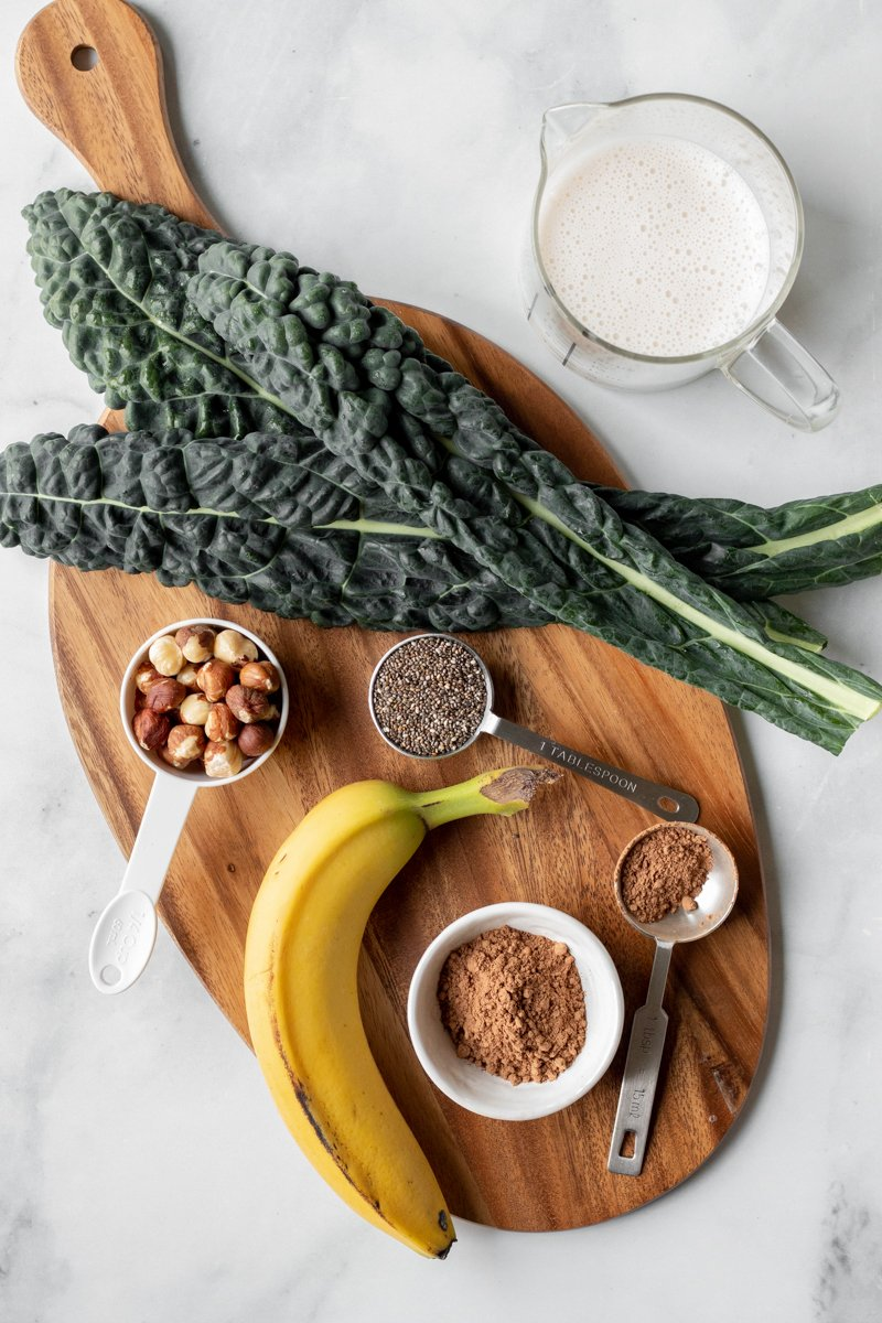 ingredients laid out on a board: banana, hazelnuts, kale, chia seeds, cacao, plant milk