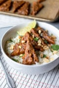 Easy baked Peanut Tempeh in a bowl with rice and lime wedge