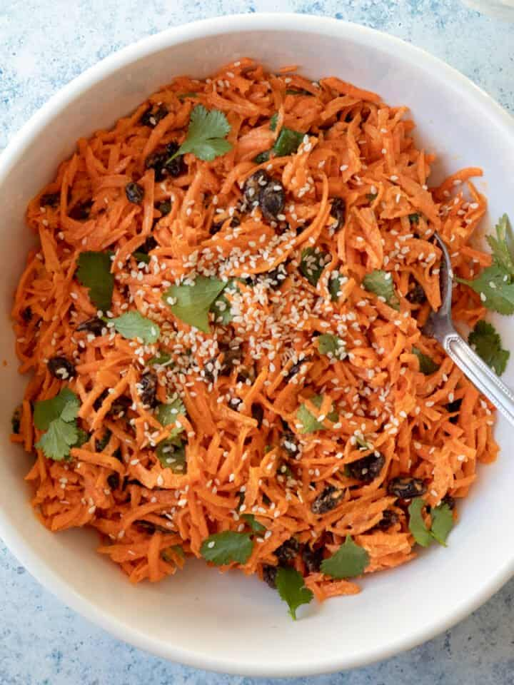 overhead view of carrot salad in large white serving bowl.
