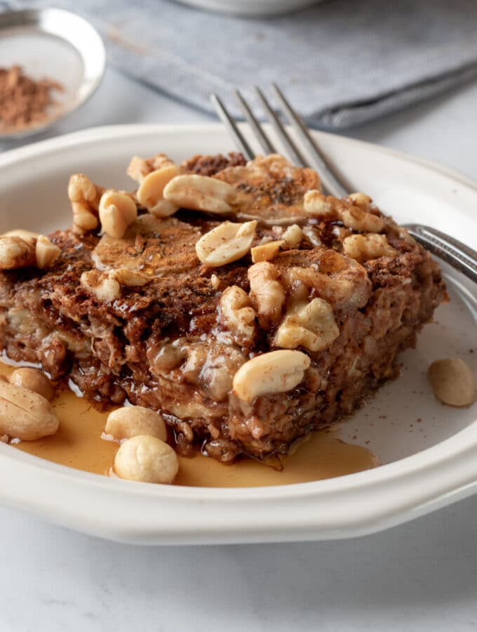 baked oatmeal on a white plate drizzled with maple syrup