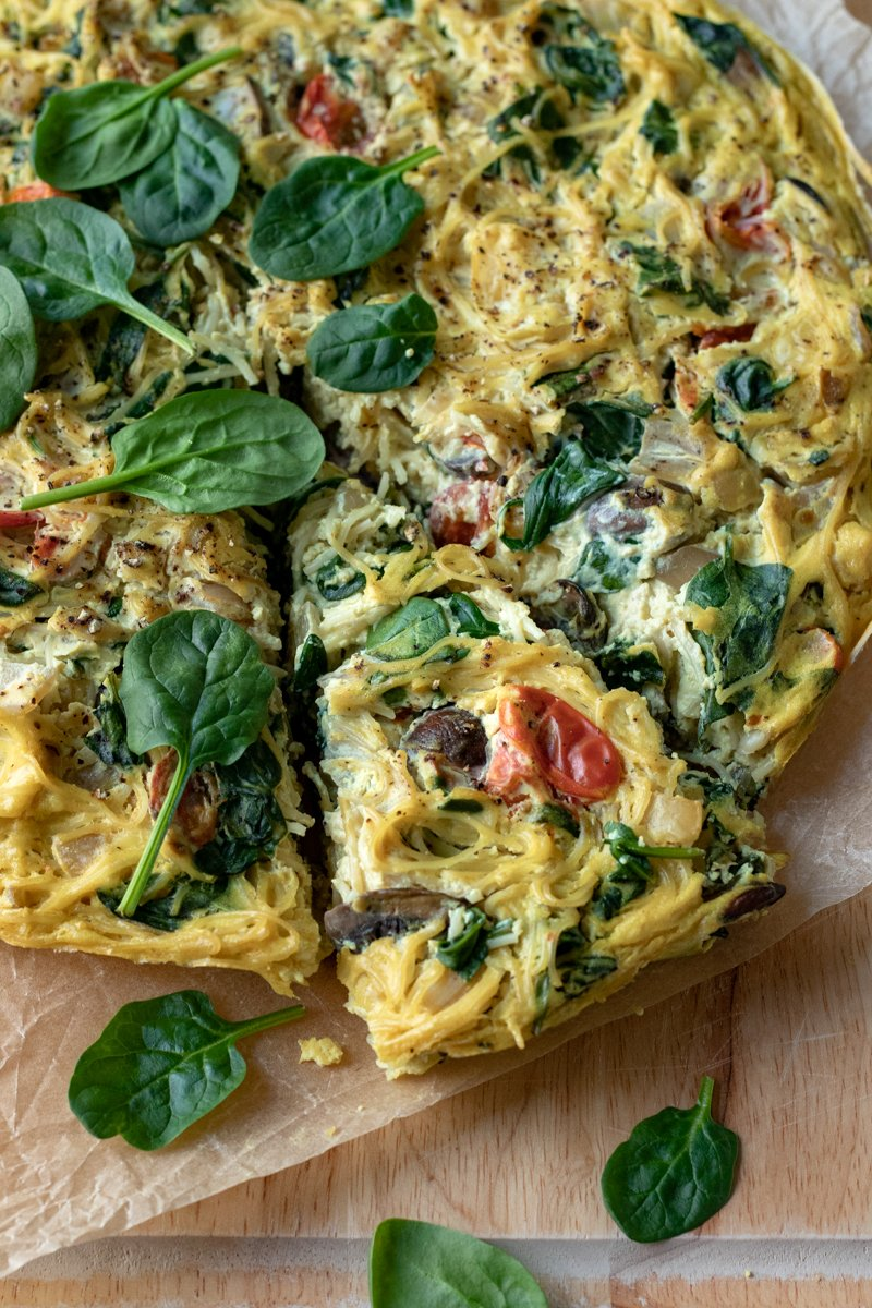 pasta frittata on a cutting board topped with a handful of fresh spinach