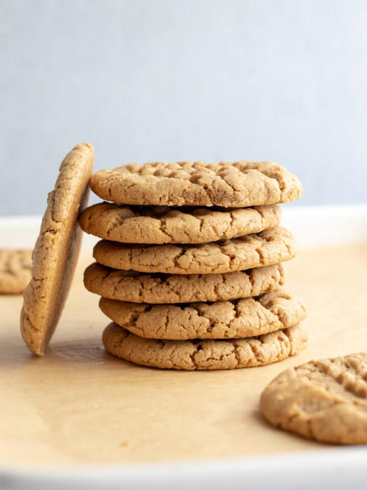 a stack of 6 cookies with one cookie leaning against the side