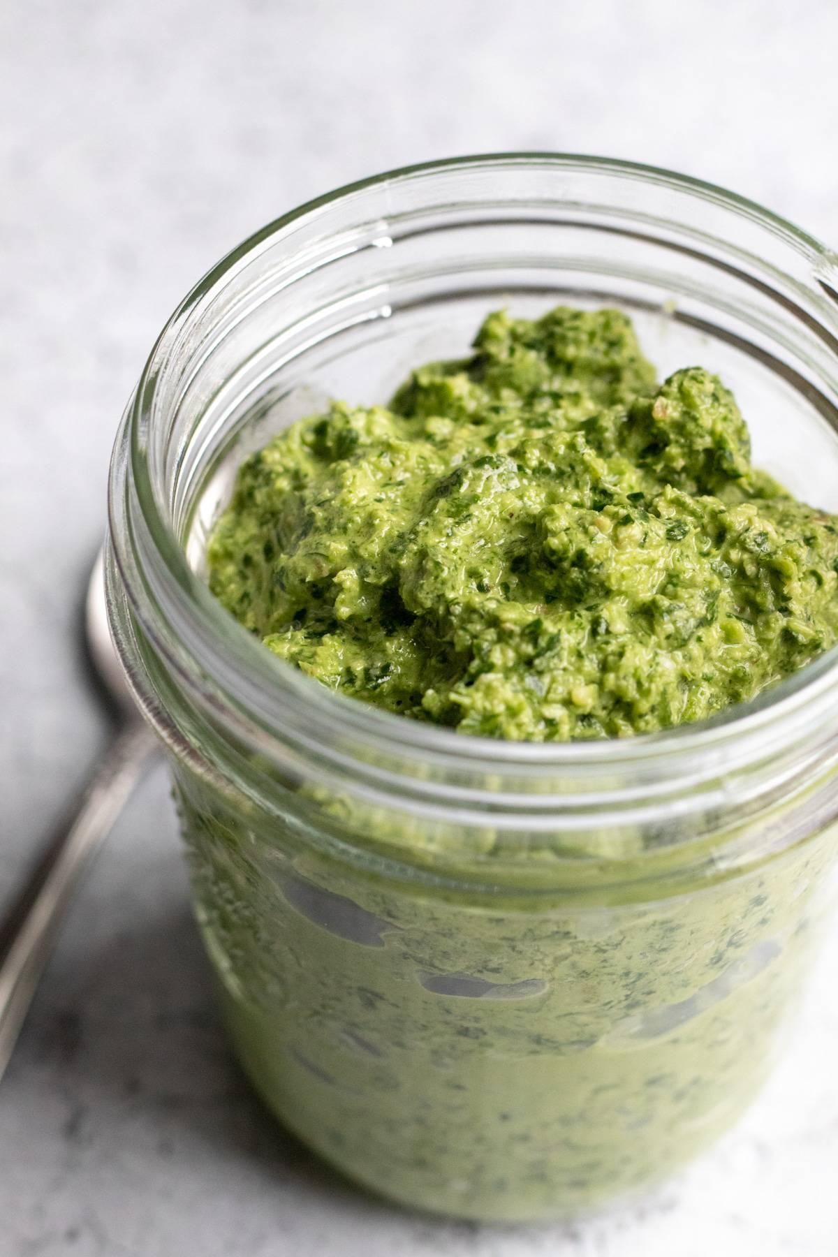 colorful green pesto in a glass jar