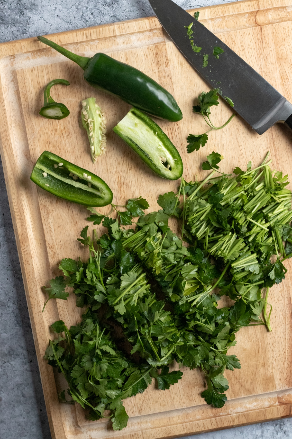 roughly chopped parsley and jalapeños on a cutting board