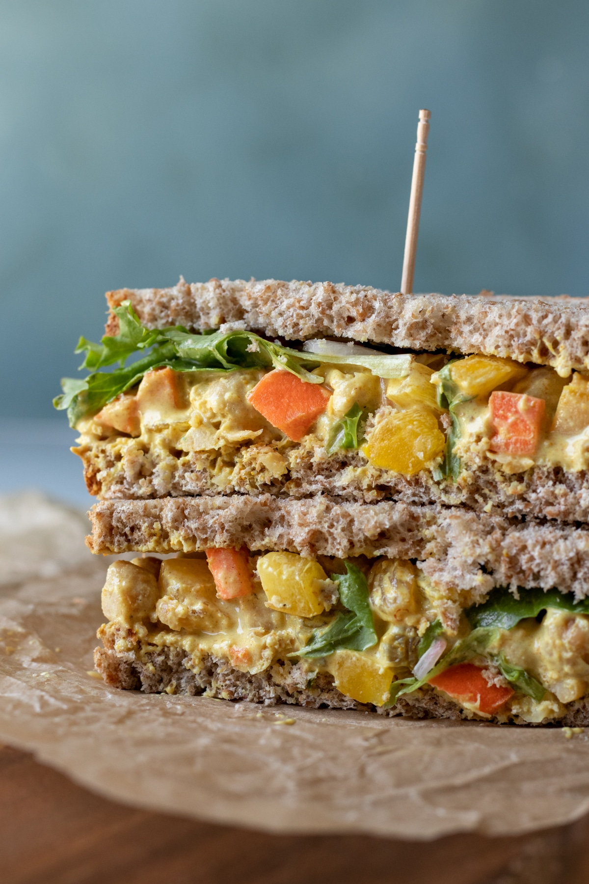 a chickpea salad sandwich cut in half and stacked showing all the veggies inside