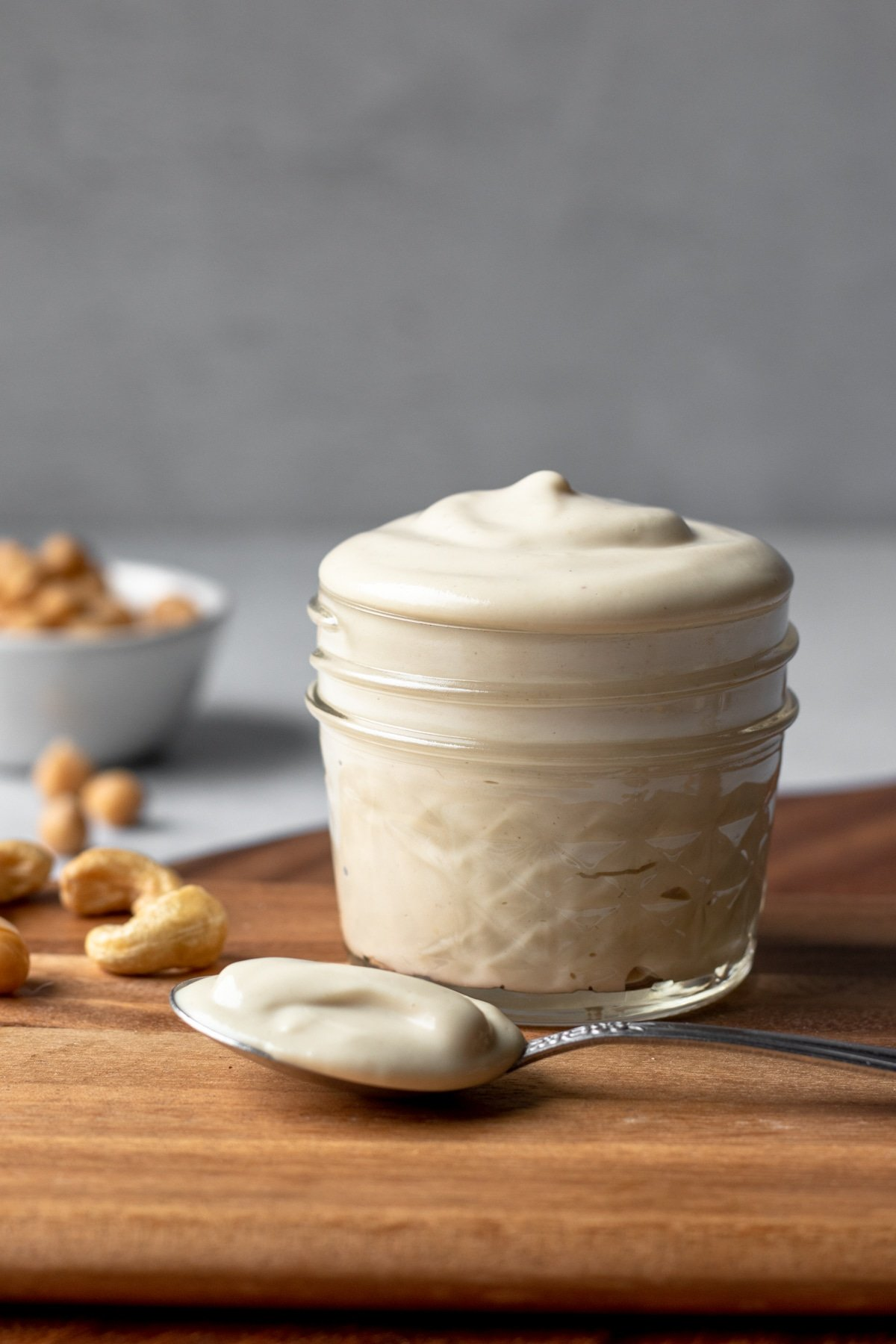 homemade oil-free vegan mayo in a small jar with a spoonful of mayo resting beside it