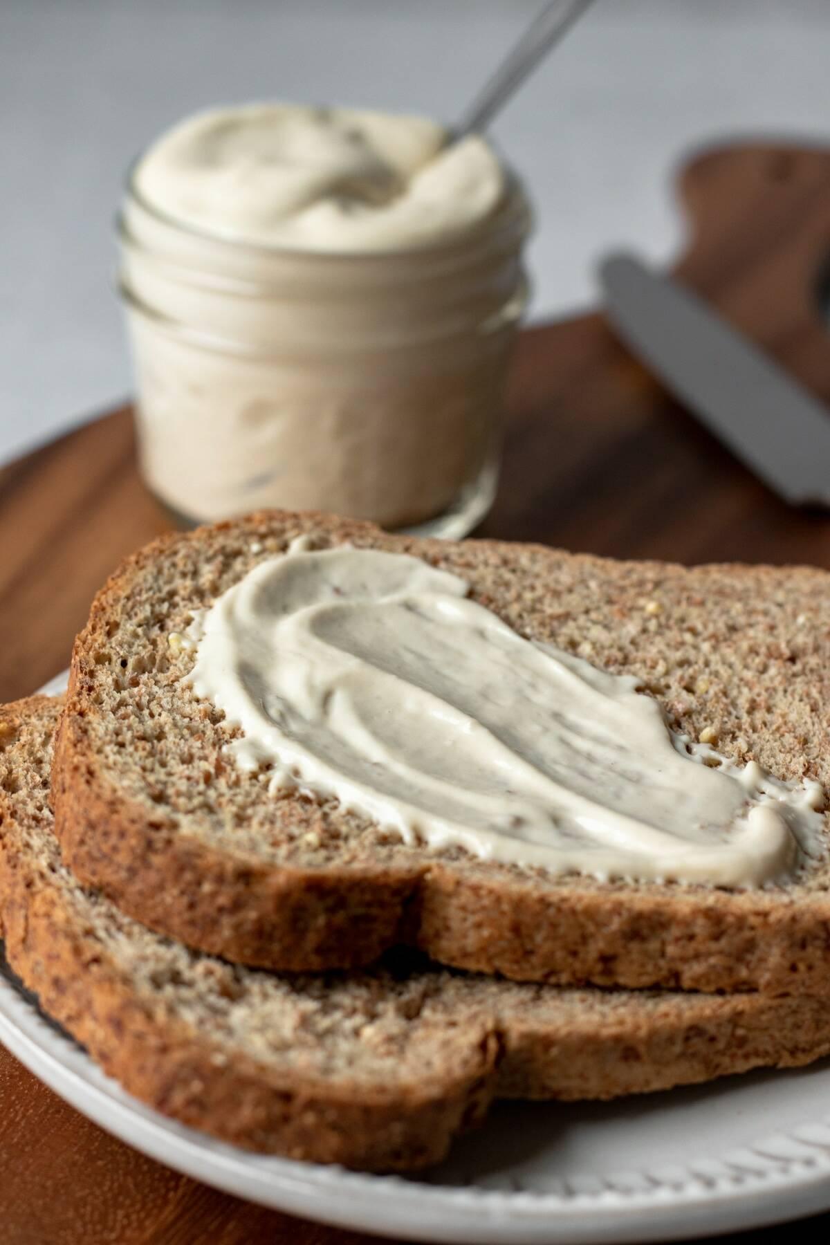 aquafaba mayo spread on a piece of toasted bread.
