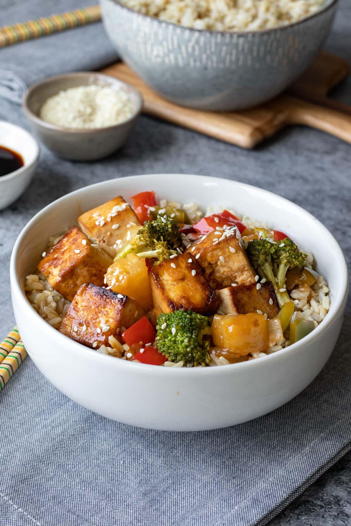 tofu, broccoli, peppers, sweet and sour sauce, rice in a white bowl