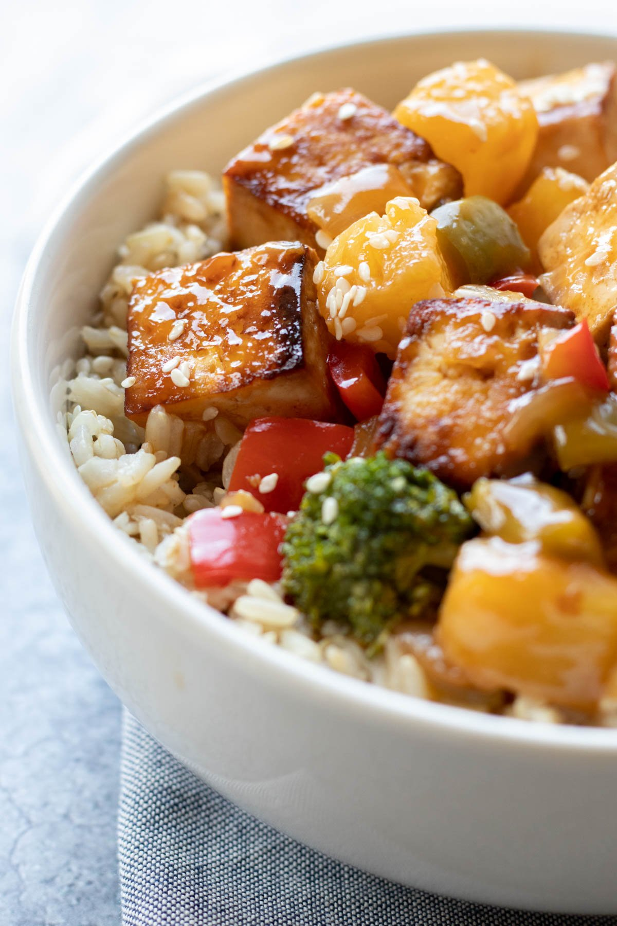 tofu and veggies on top of rice in a white bowl