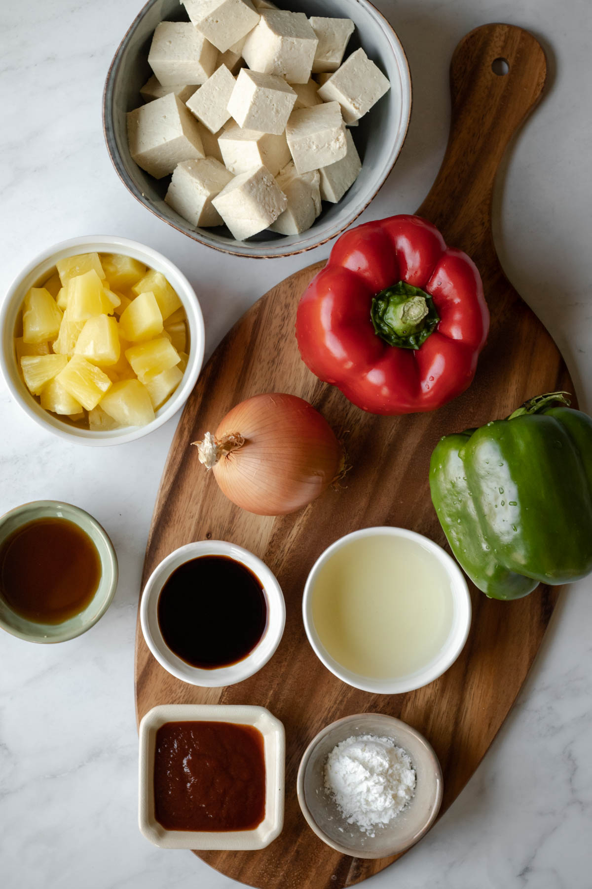 ingredients laid out on a cutting board - tofu, pineapple, red and green bell peppers, onion, tamari, ketchup, maple syrup, rice vinegar, corn starch
