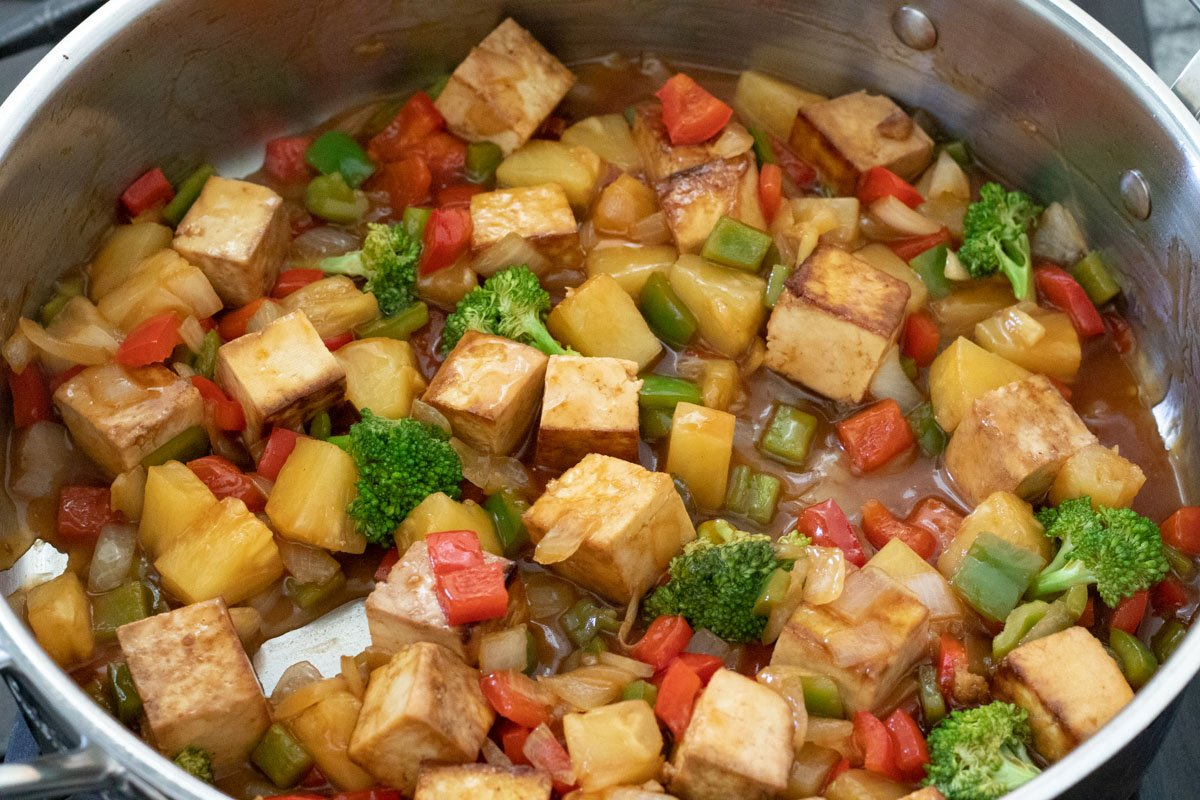 sautéed vegetables, seared tofu, and sweet and sour sauce in pan
