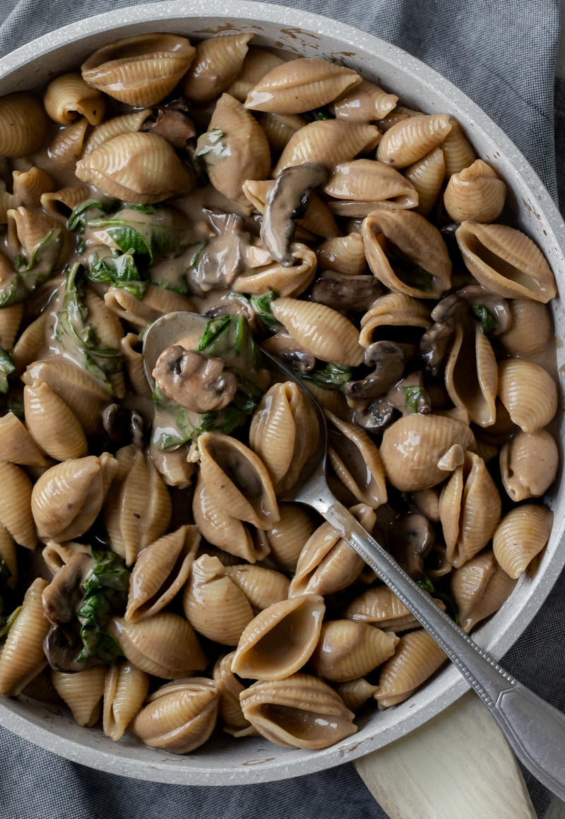 overhead close up of mushroom-colored creamy shells in a pan.