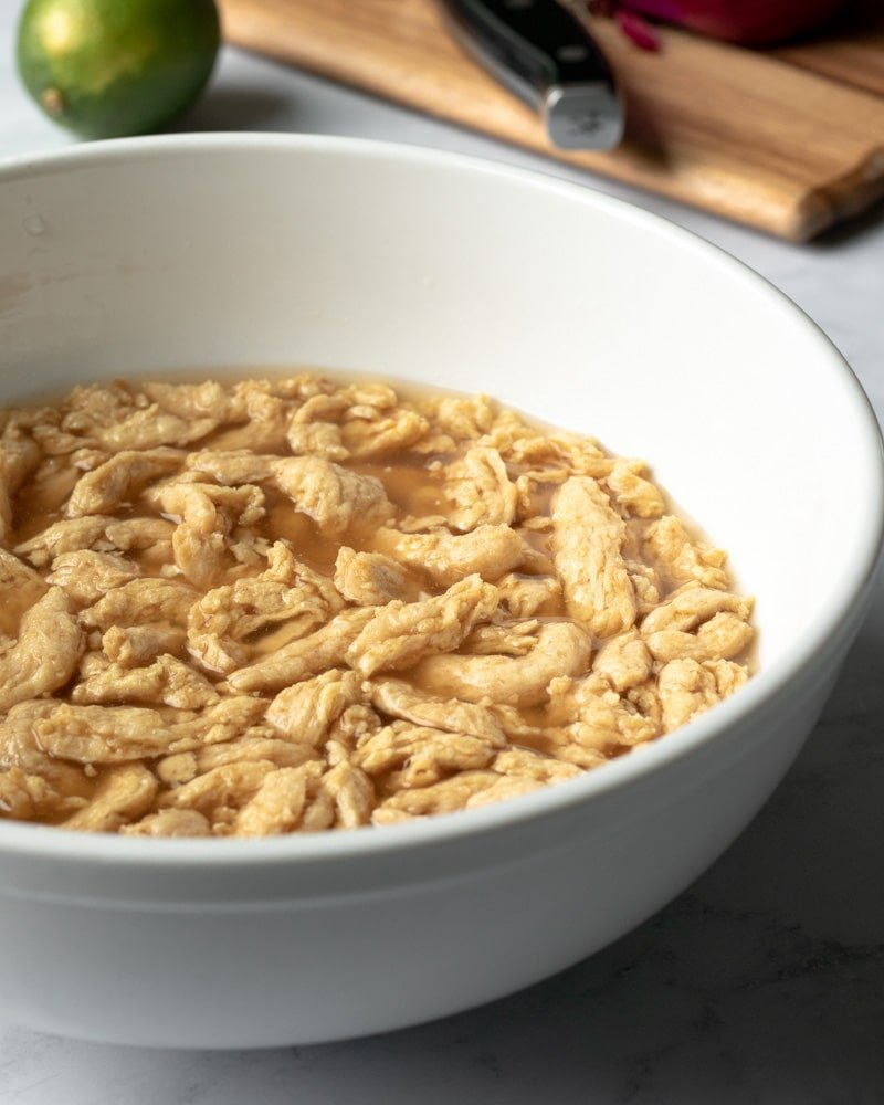 re-hydrating soy curls in a bowl full of broth