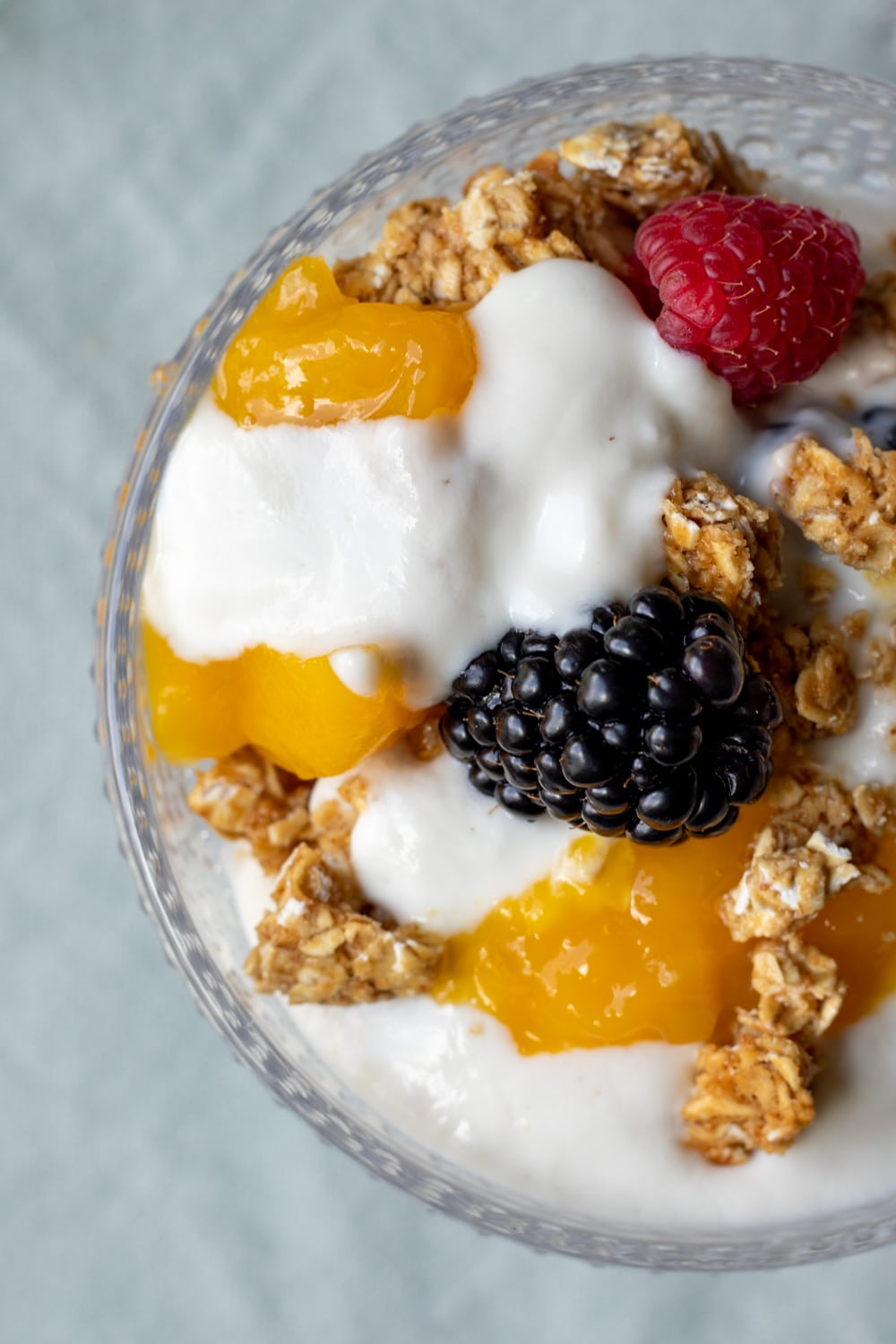 overhead view of yogurt, berries, and granola in a decorative glass bowl
