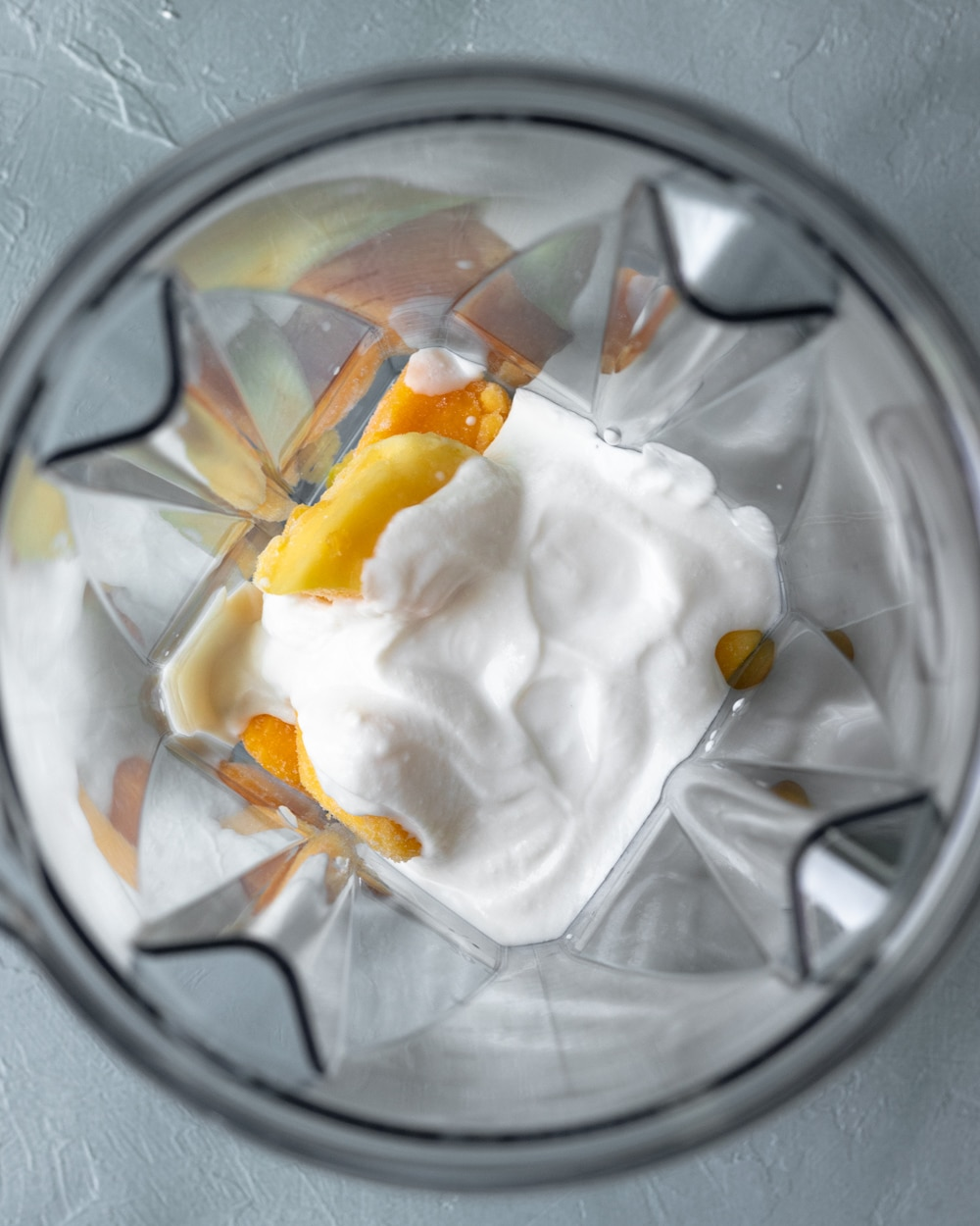 looking inside blender jar with creamy cashew yogurt poured over mango