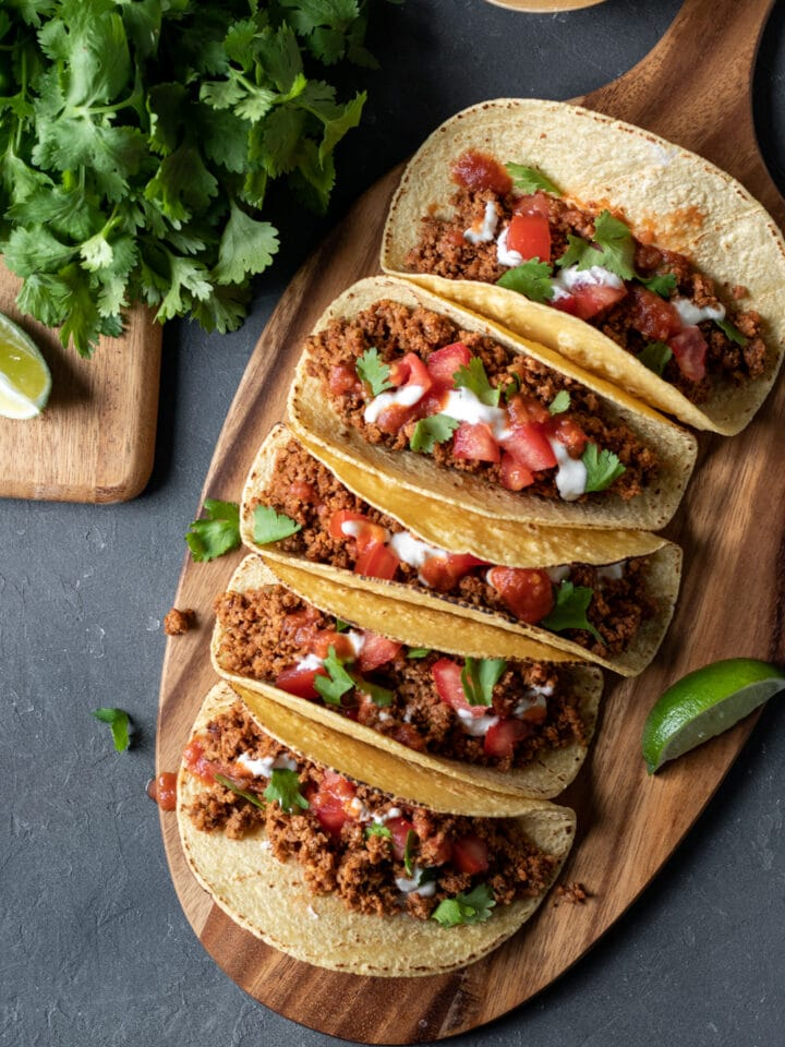 overhead view of five tacos lined up on a wooden board