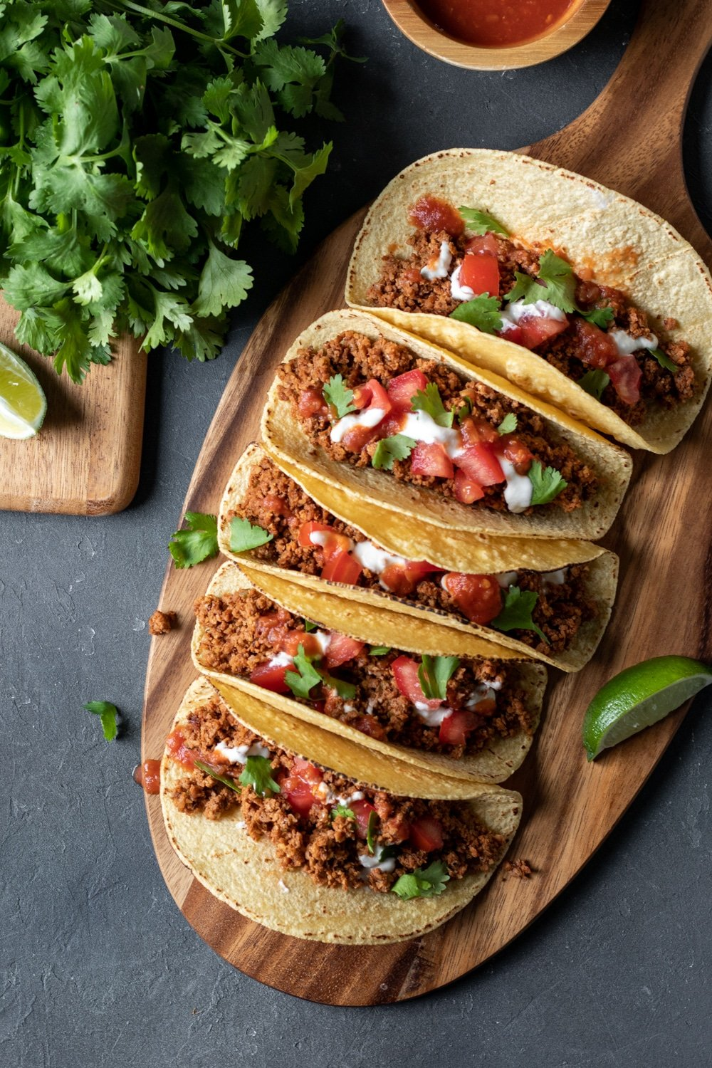 overhead view of five vegan tacos lined up on a wooden board