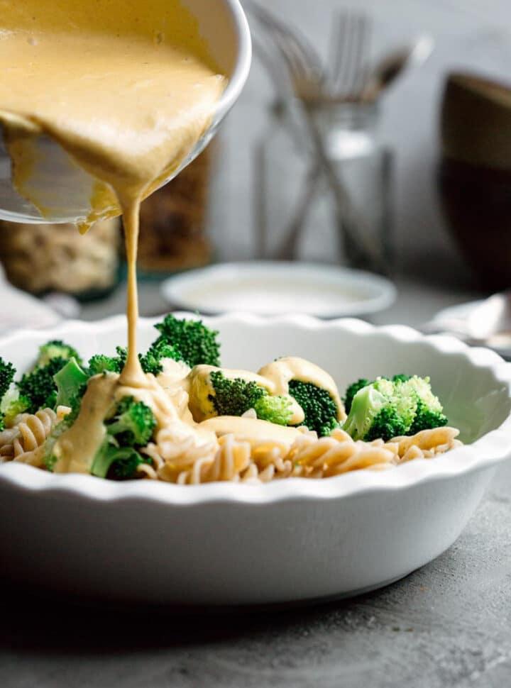 pouring creamy sauce onto pasta and broccoli