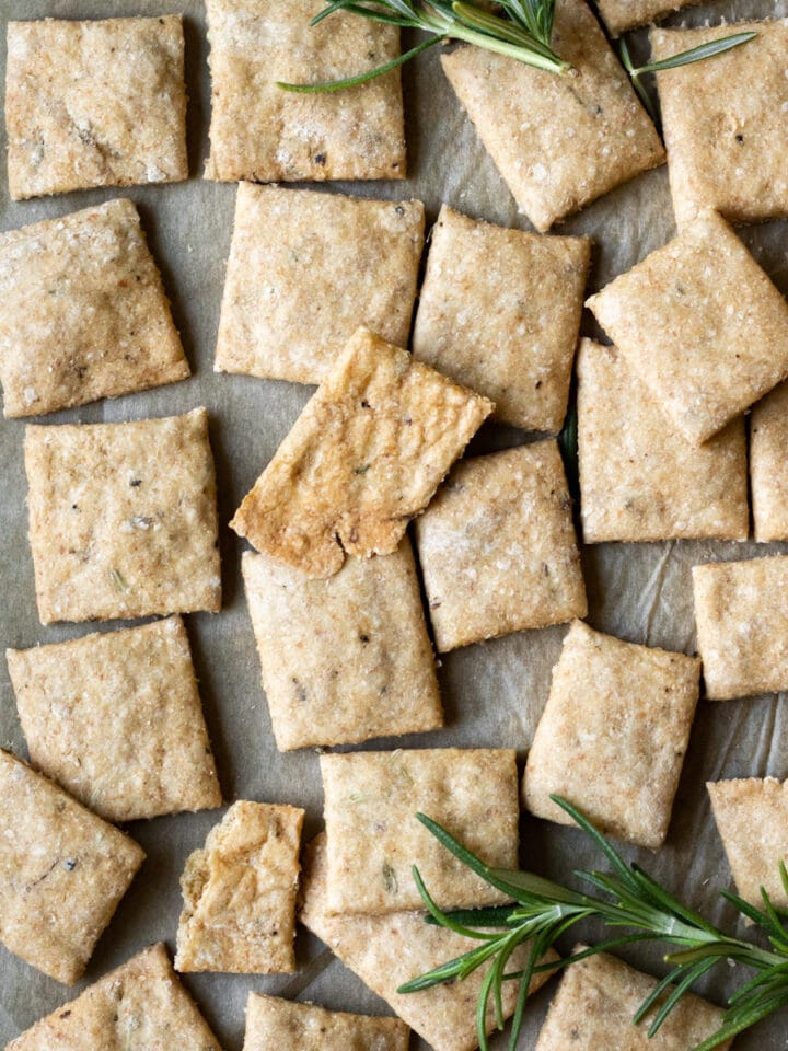 crackers and sprigs of rosemary on a baking sheet