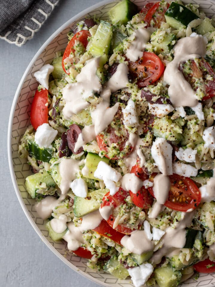 overhead view of creamy orzo salad with dressing drizzled on top