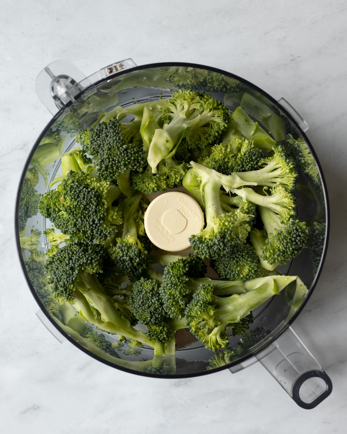 food processor bowl filled with broccoli florets