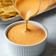 close up shot of pouring creamy cashew cheese sauce