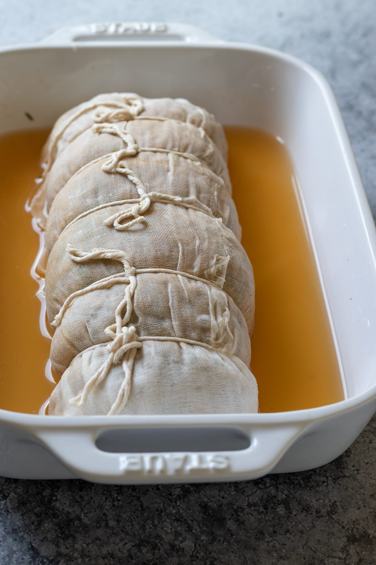 wrapped in cheese cloth, tied with twine, resting in broth in a baking dish