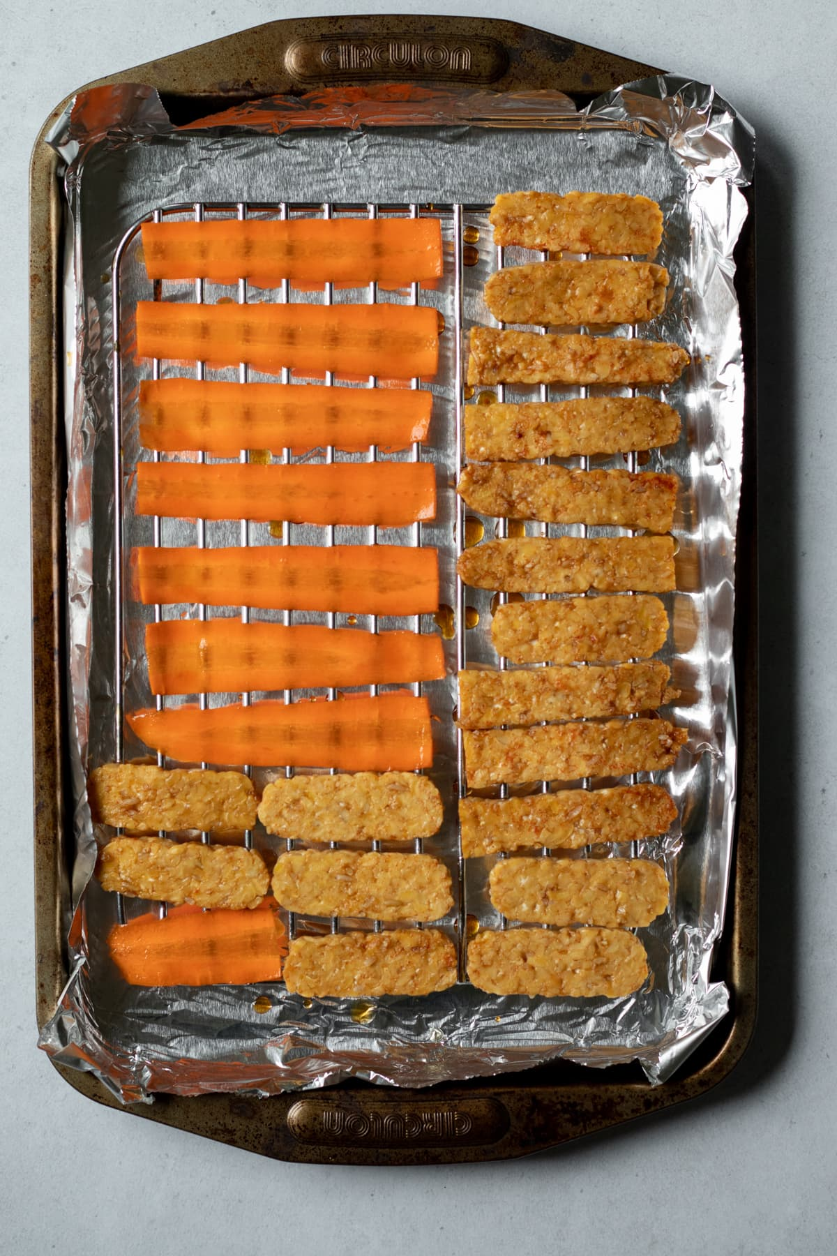 tempeh and carrot lined up on a rack on a baking sheet