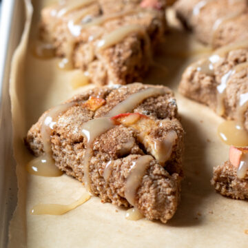 apple cinnamon scones drizzled with maple glaze on a baking pan