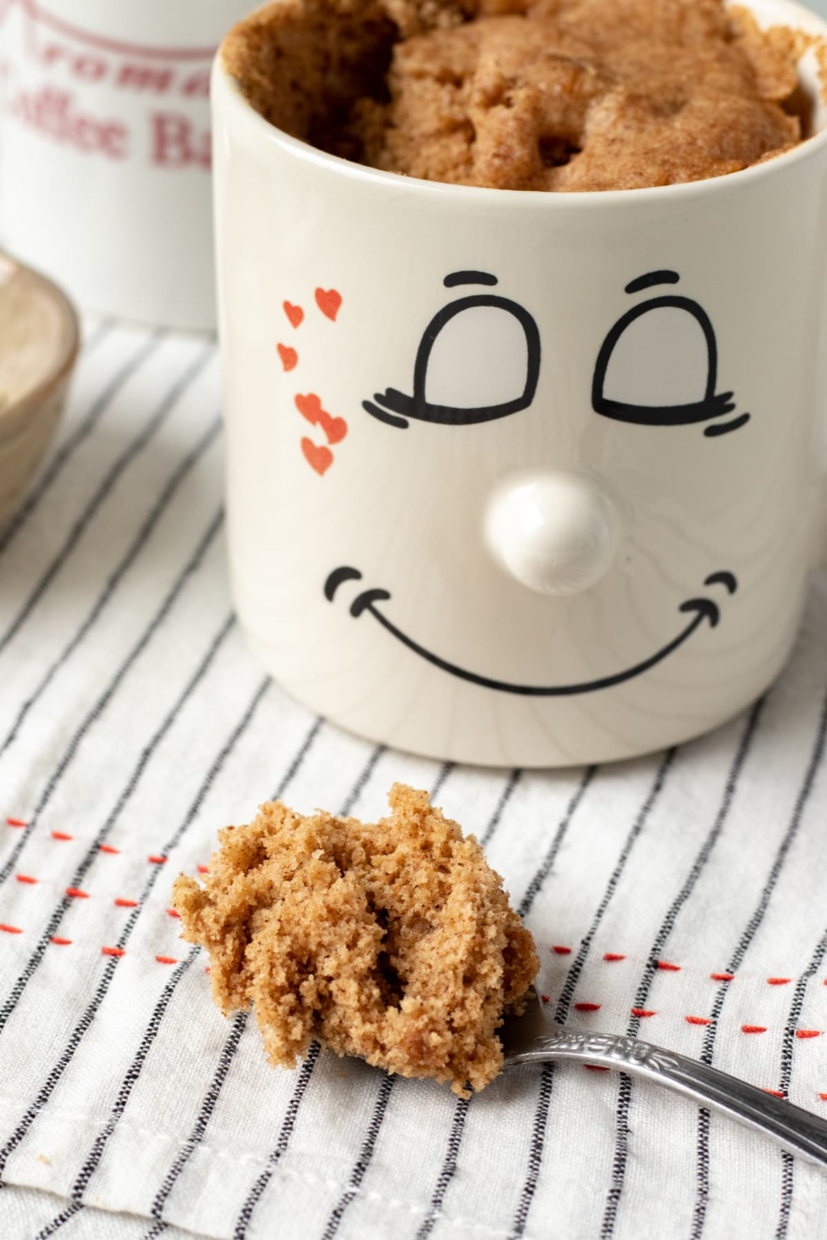 spoonful of mug cake resting in front of a cute mug with a smiley face on it