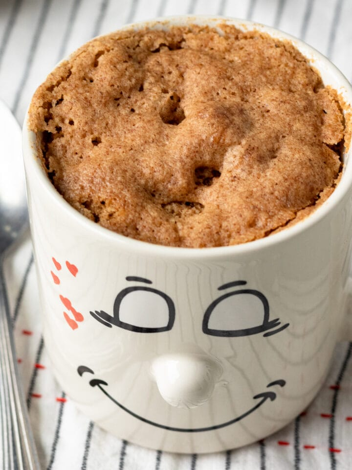 close up of healthy vegan mug cake in a cute smily face mug