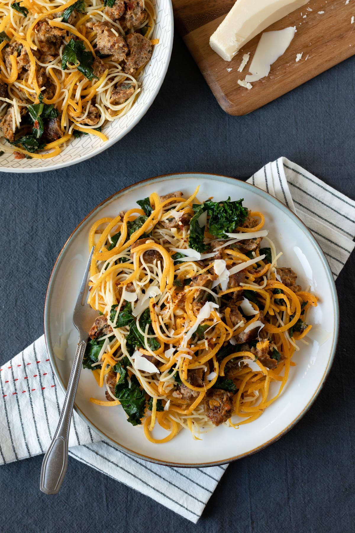 topped with vegan parm, the noodle dish on a plate