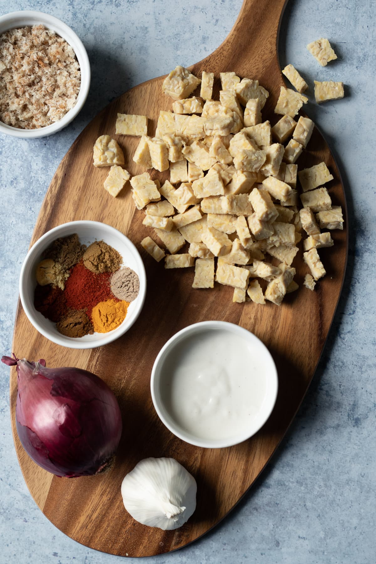ingredients laid out on a wooden board - tempeh, onion, spices, yogurt, garlic, breadcrumbs