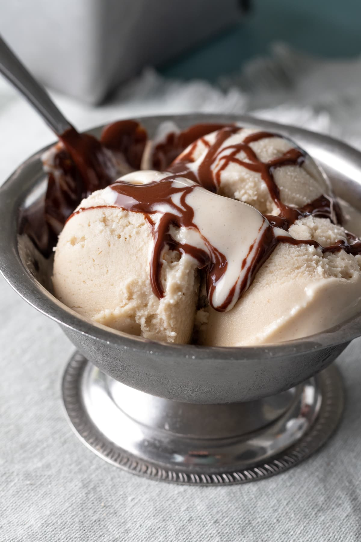 chocolate syrup drizzled on vanilla ice cream in a bowl