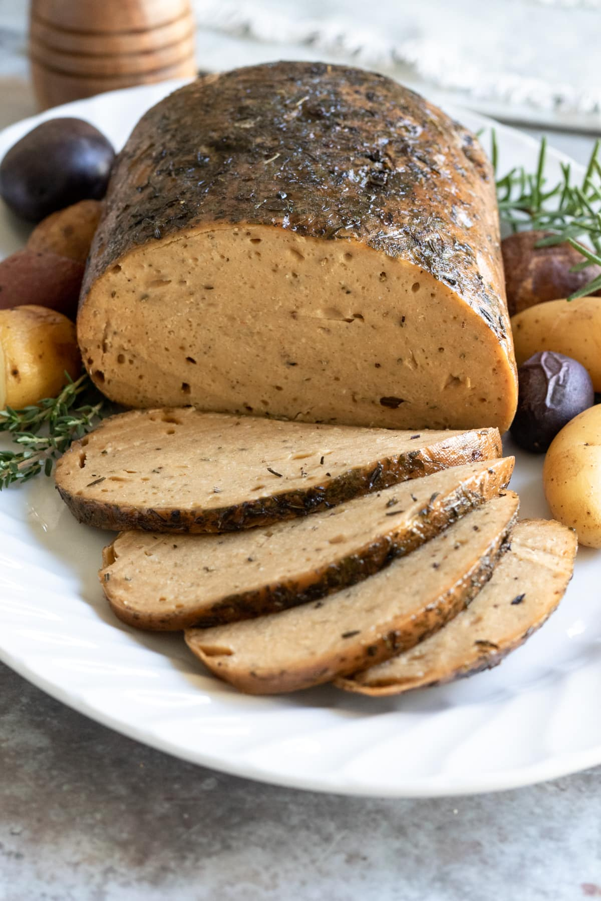 sliced seitan turkey roast on a platter showing the texture of the skin