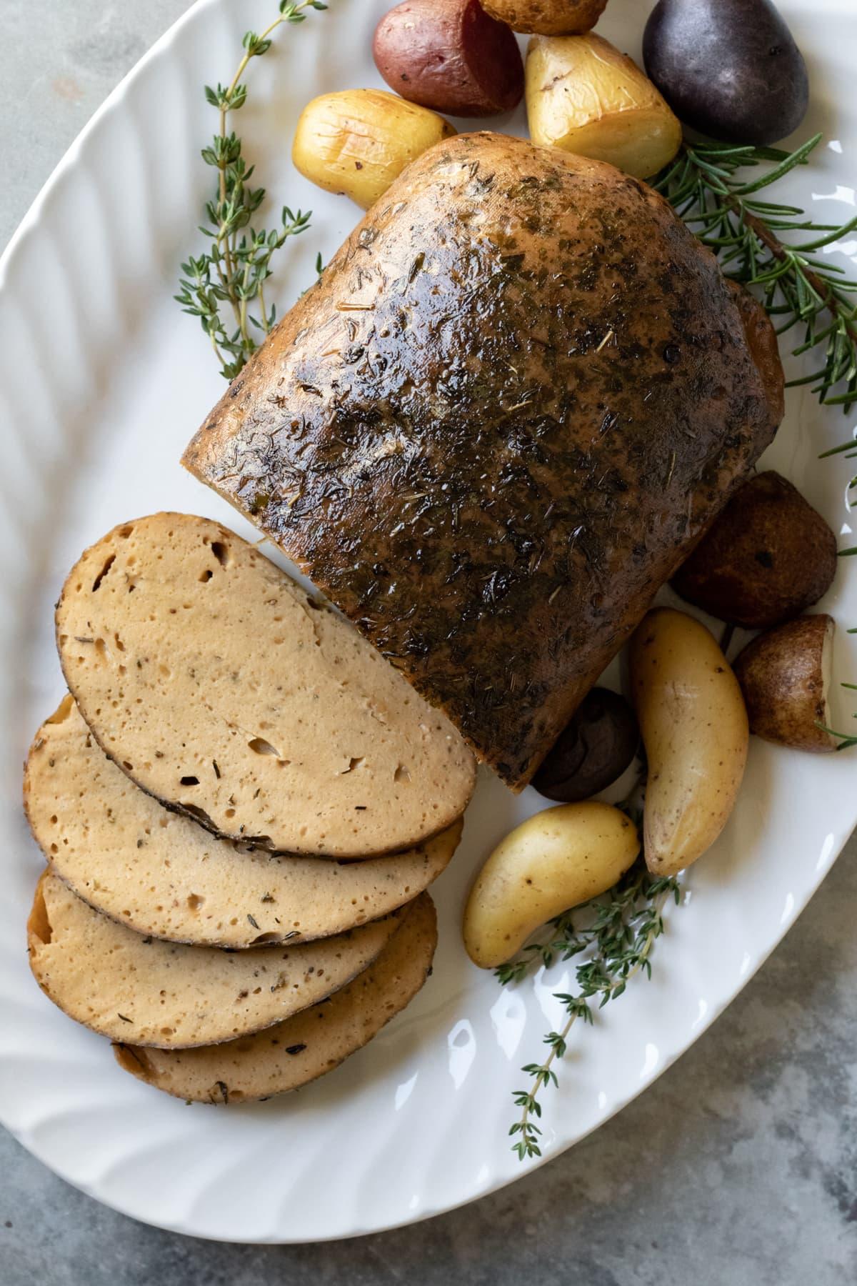 seitan turkey roast on a platter with herbs and potatoes