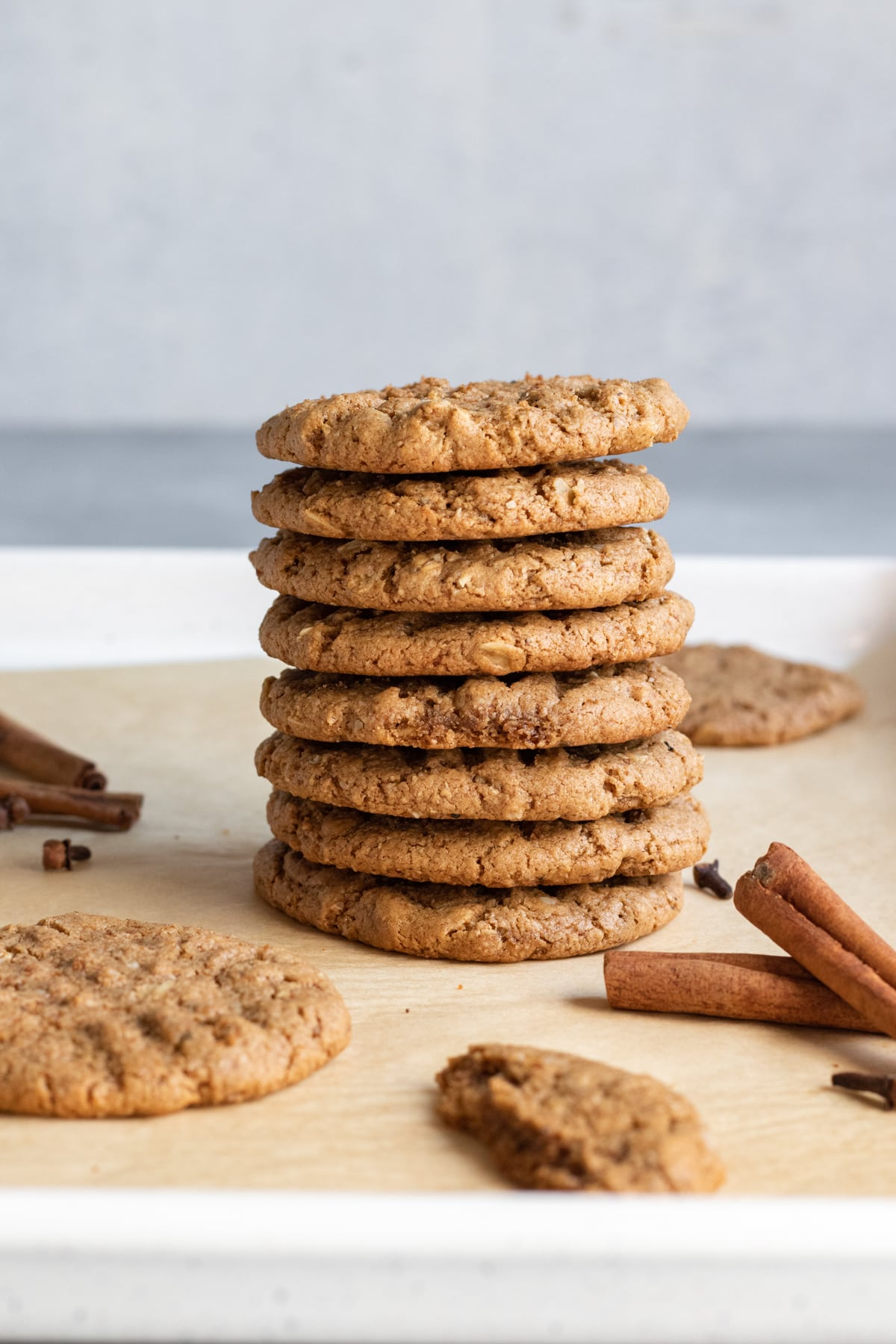 a stack of spicy vegan oatmeal cookies with cinnamon sticks and cloves nearby