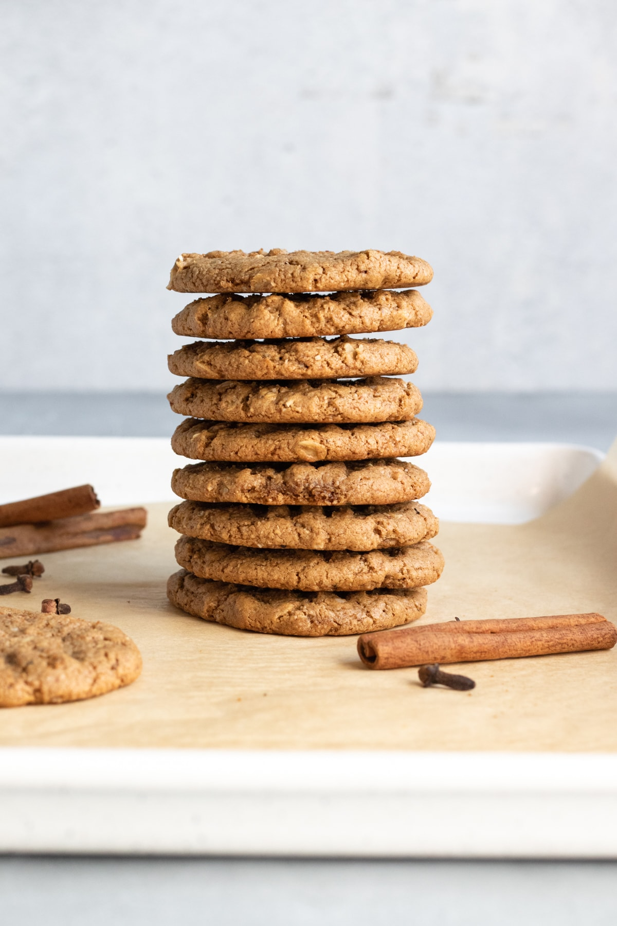 a tall stack of cookies on a baking sheet with cinnamon sticks and cloves