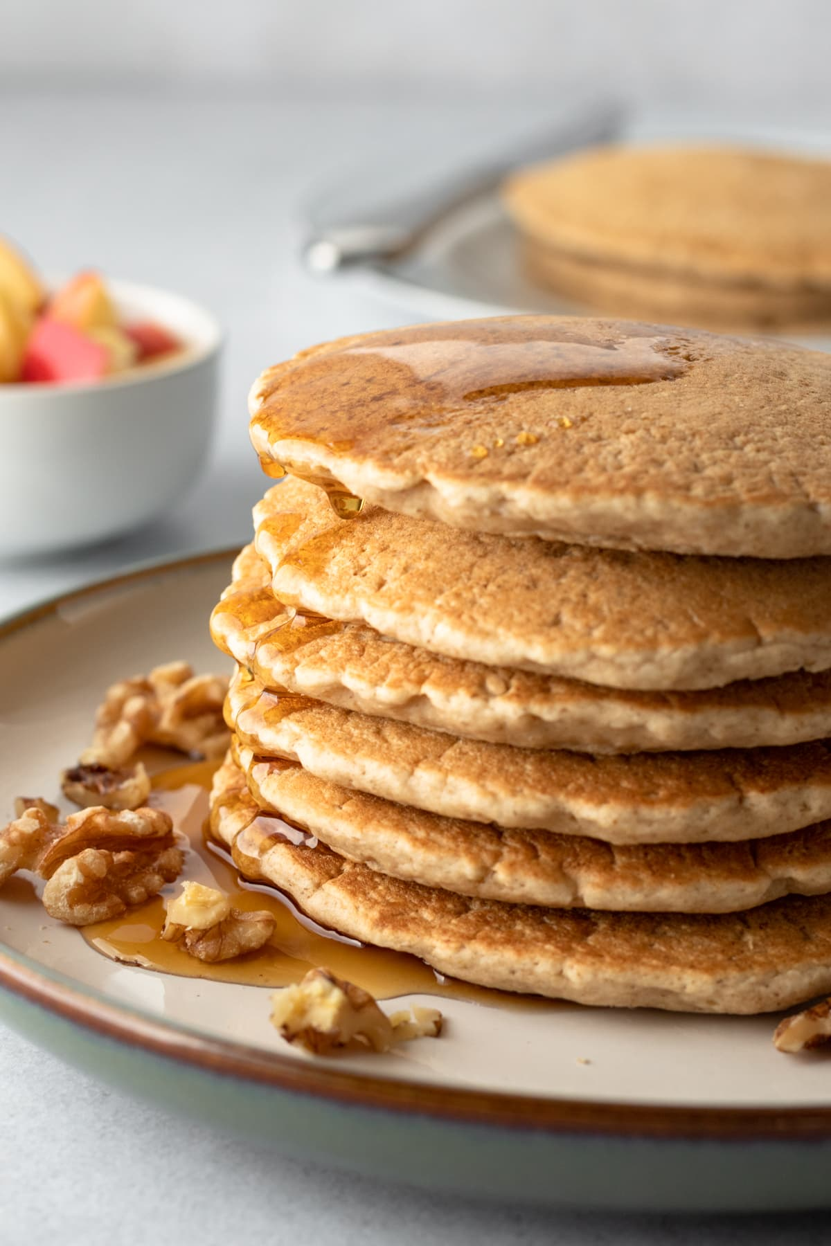 a stack of pancakes with walnuts and maple syrup