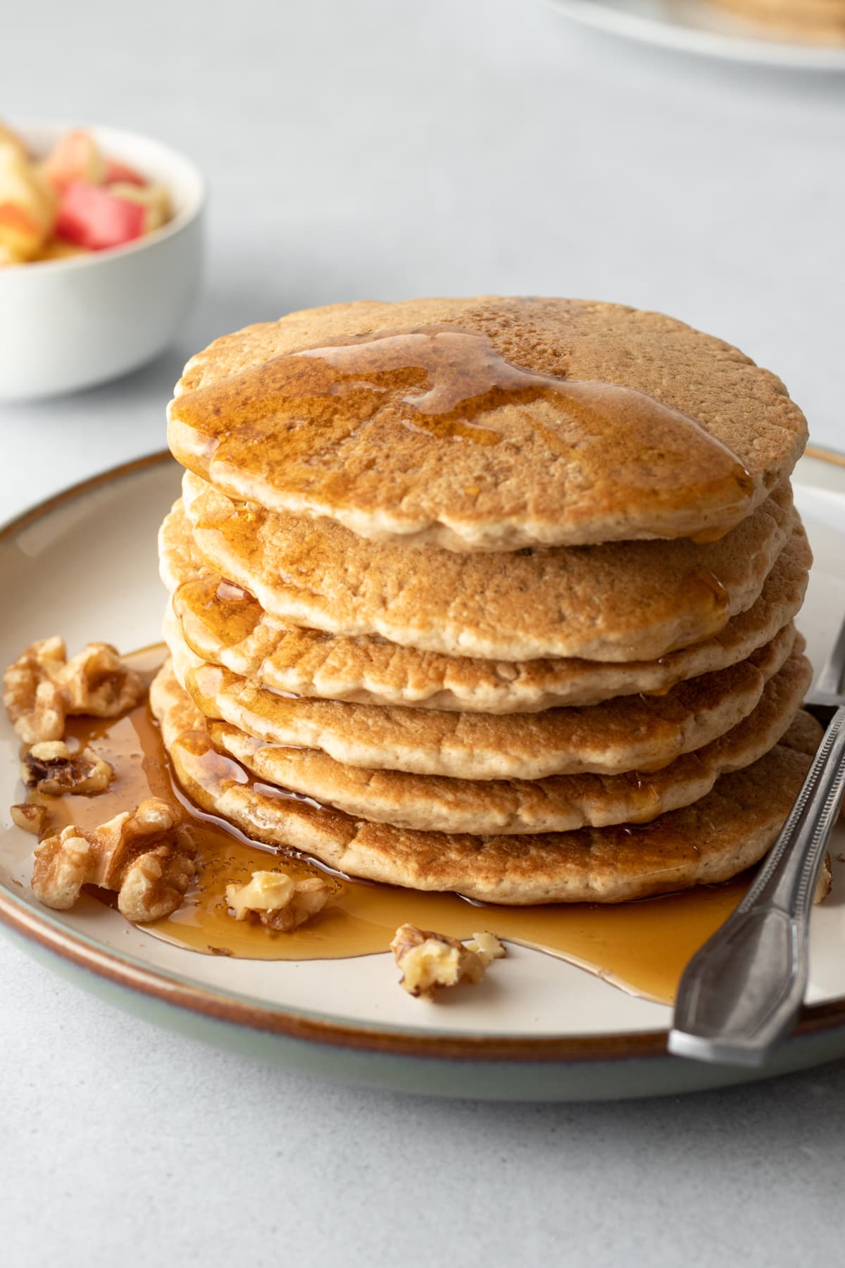 a stack of golden pancakes drizzled with maple syrup