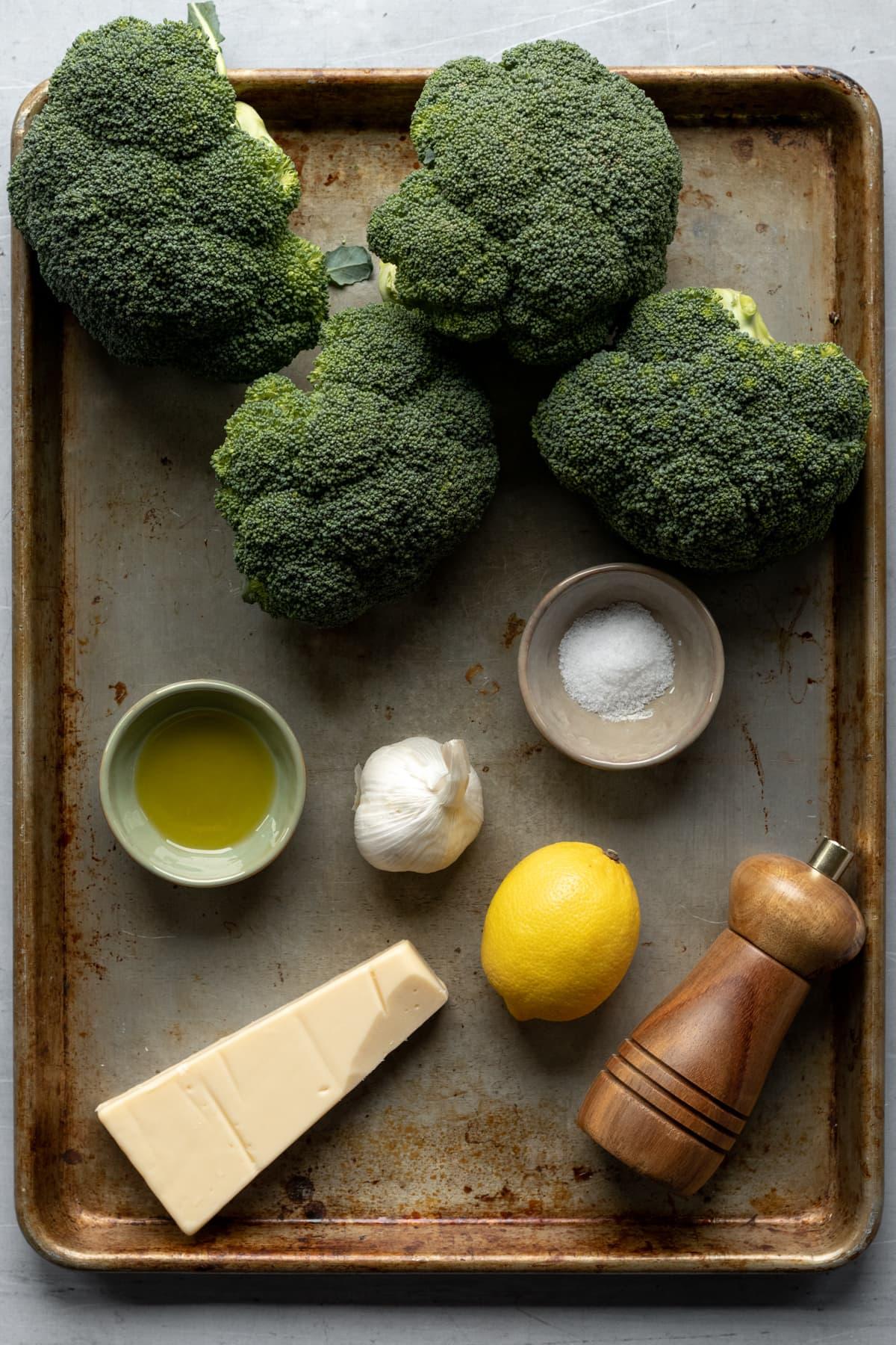 broccoli, garlic, lemon, oil, salt, pepper, and vegan cheese on a baking sheet