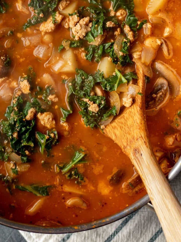 wooden spoon in soup in a pot