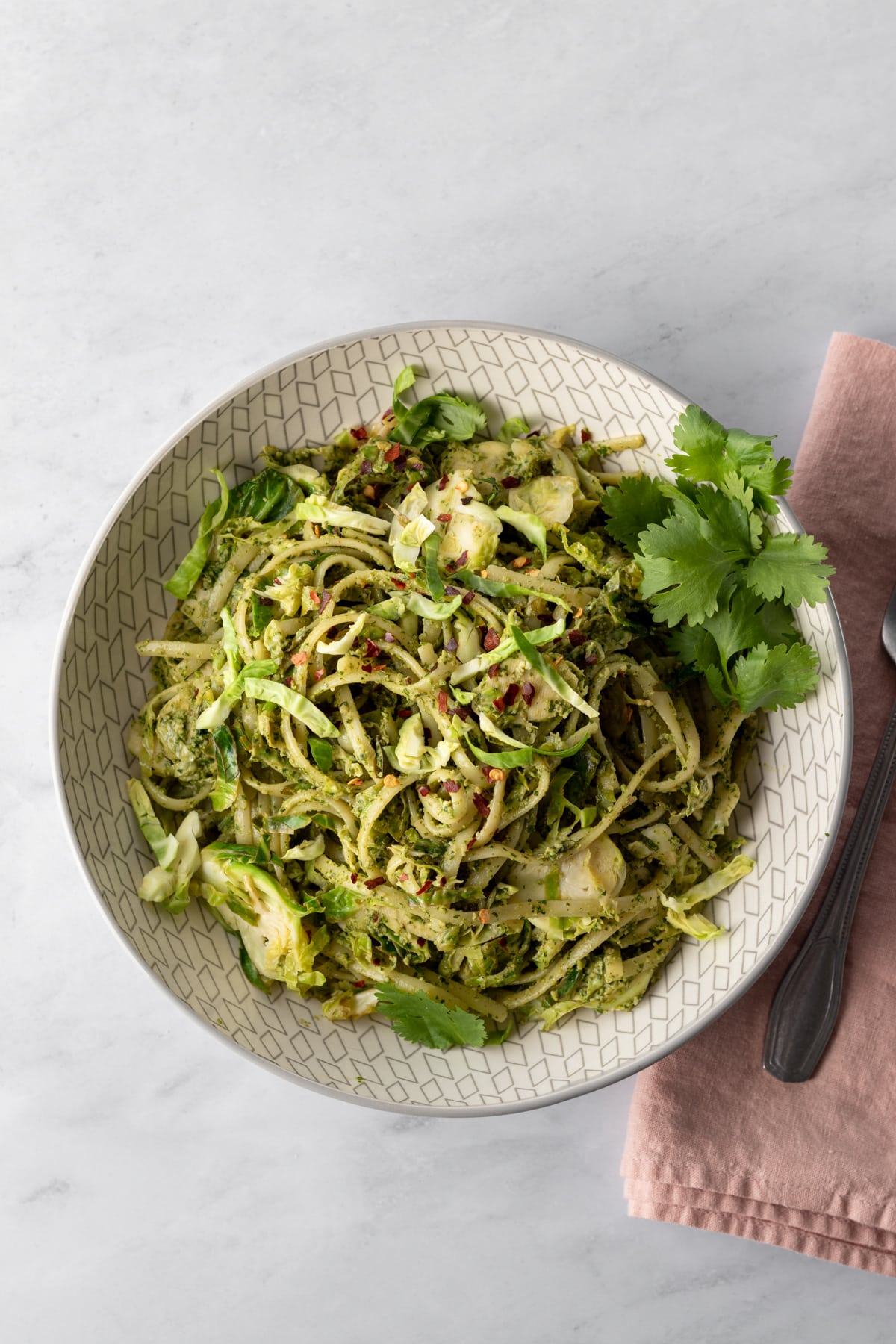 serving of pasta and shredded brussels sprouts coated with zhoug, aka spicy cilantro pesto