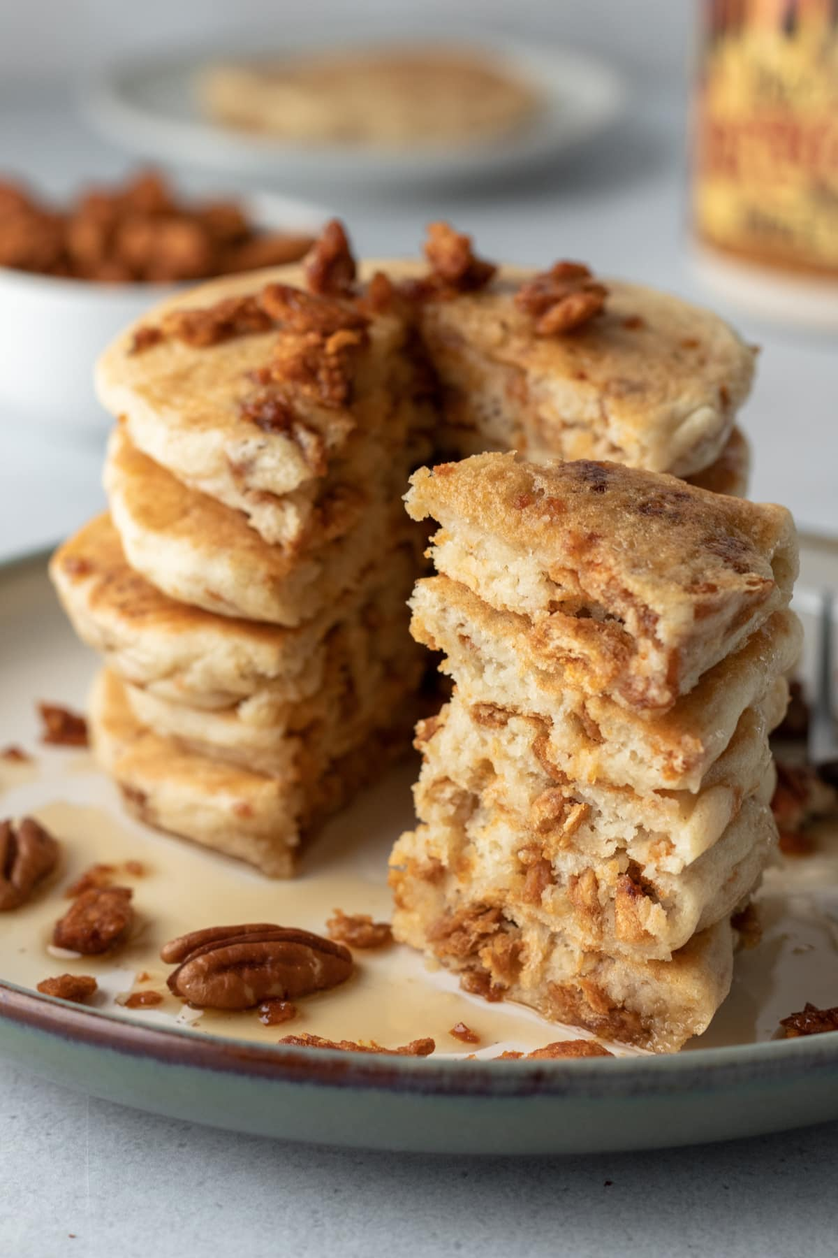 a tall stack of pancakes with vegan bacon crumbled on top