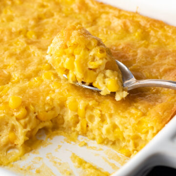 creamy corn pudding in a white baking dish