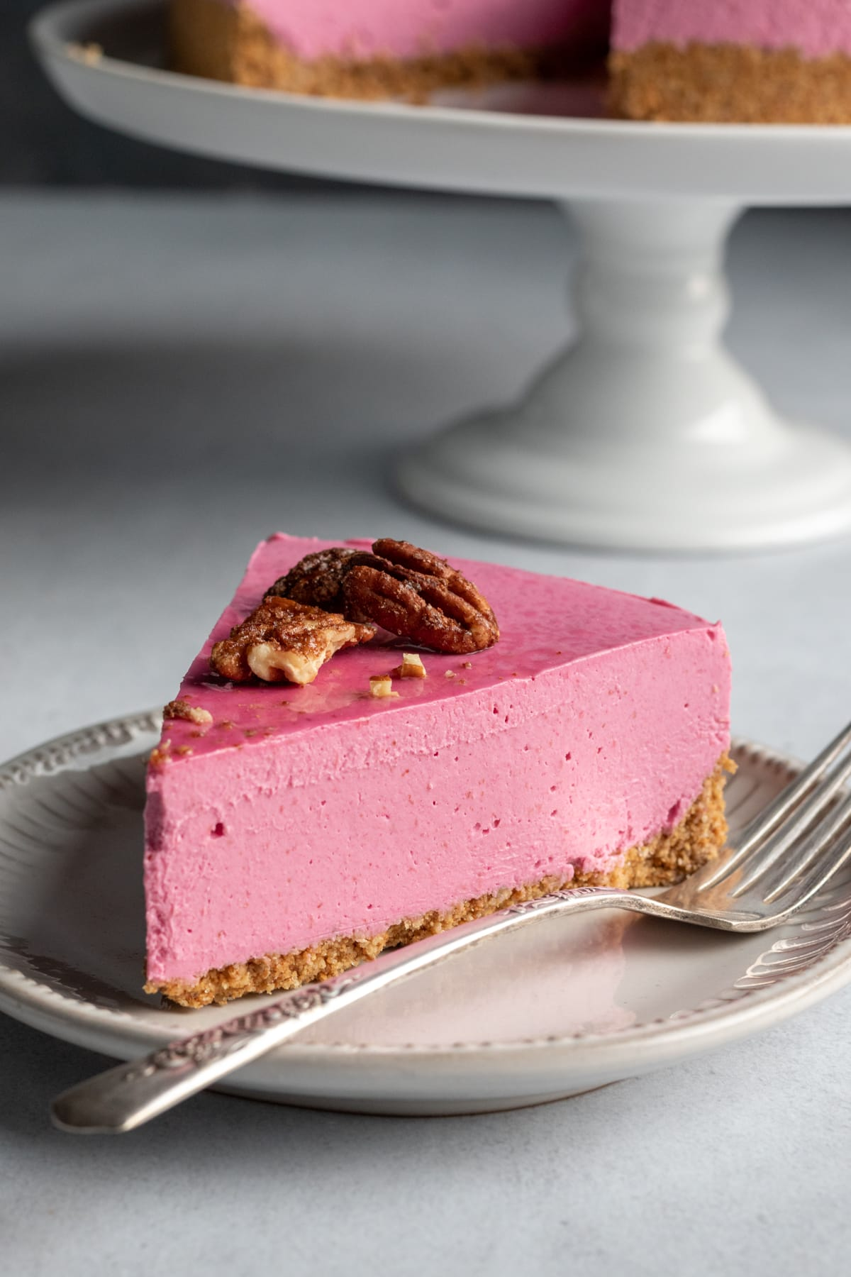 a tall slice of pink cranberry cheesecake on a plate