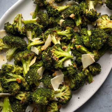 roasted broccoli on a serving platter tossed with vegan parmesan