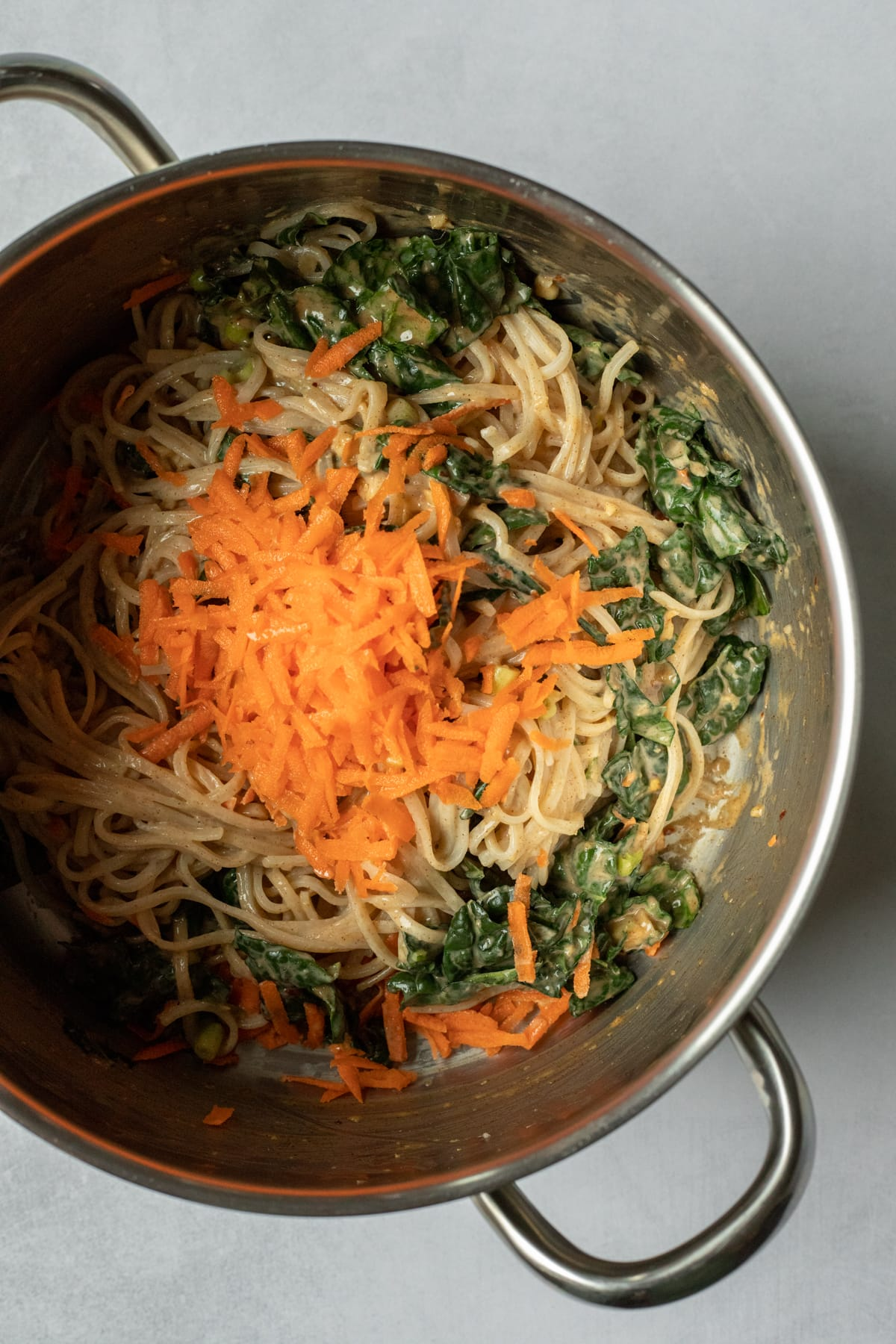 combining cooked noodles, veggies and sauce in a pot