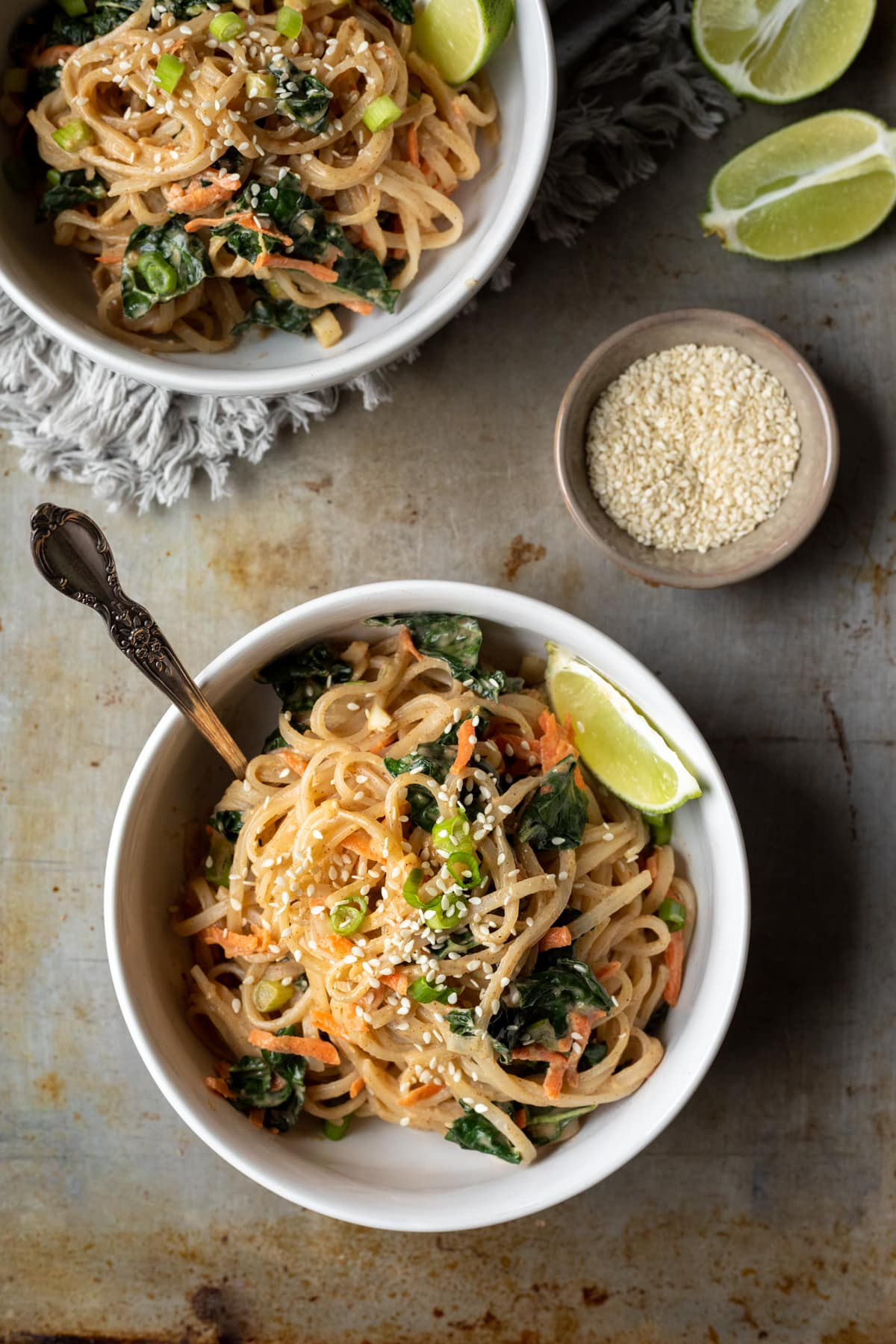 two servings of noodles in white bowls topped with green onion and lime wedge